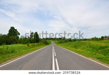 Highway in Russia in summer. The road goes downhill and turns left