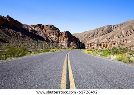 Highway into mountains in Death Valley National Park - stock photo
