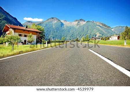 highway leading to mountains - stock photo