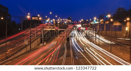 highway motor road of big city with heavy traffic blurred lights at sunset panoramic