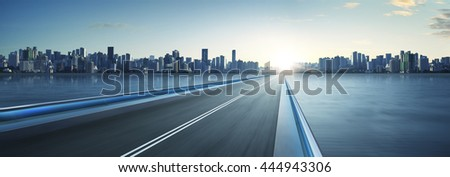 Highway overpass motion blur with city skyline background . cold mood . horizontal. - stock photo