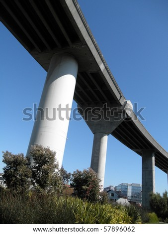 Highway overpass on large pillars towers over park below in San Francisco Mission Bay area - stock photo