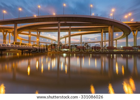 Highway overpass ring intersection during twilight river front view - stock photo