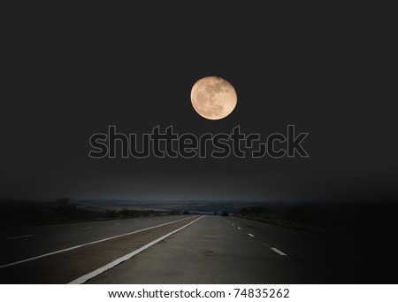 Highway passing through desert in moon light - stock photo