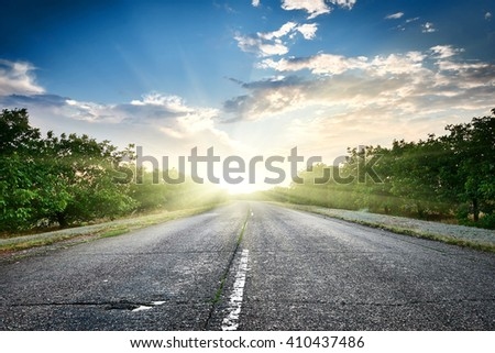 highway road at sunset, travel and transportation concept, cloudy sky and sun on horizon, beautiful summer landscape