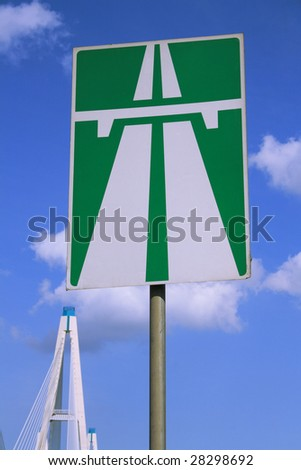 Highway road sign with towers of the bridge on the background