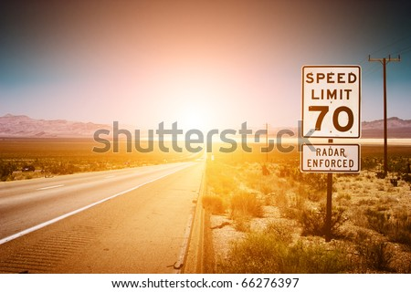 Highway road to sunset. 70 MPH speed limit sign. - stock photo
