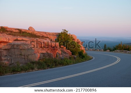 Highway rounds a curve as the sunrise kisses the pink granite rock face turning it into fire