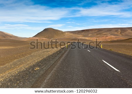 Highway through dry gravel lava field landscape under a blue summer sky. Highlands of Central Iceland. - stock photo