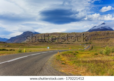 Highway through Iceland landscape at foggy day. Horizontal shot - stock photo