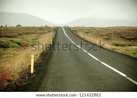 Highway through Iceland landscape at foggy day. Toned vignetted image - stock photo
