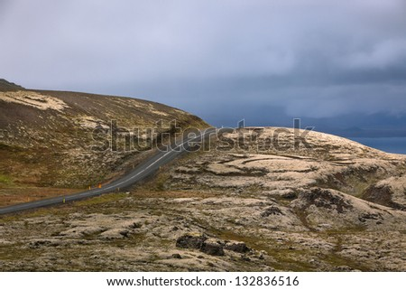 Highway through Iceland landscape at overcast day. Horizontal shot - stock photo