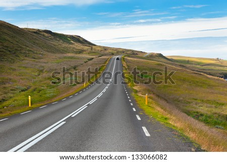 Highway through Icelandic landscape under a blue summer sky. Horizontal shot - stock photo