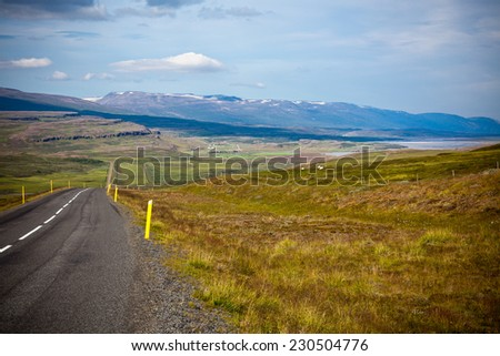 Highway through Icelandic landscape under a blue summer sky with clouds - stock photo