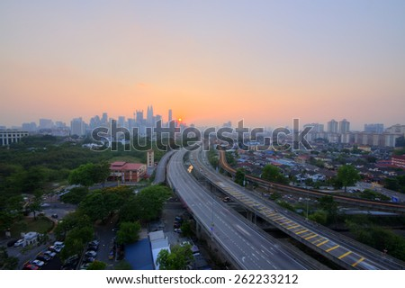 Highway to Kuala Lumpur city during sunset Image has grain or blurry or noise and soft focus when view at full resolution. (Shallow DOF, slight motion blur) - stock photo