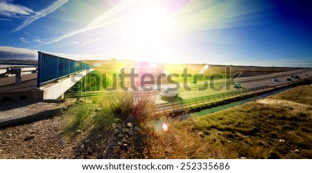 Highway traffic and sunset.Sunbeam and bridge over road - stock photo