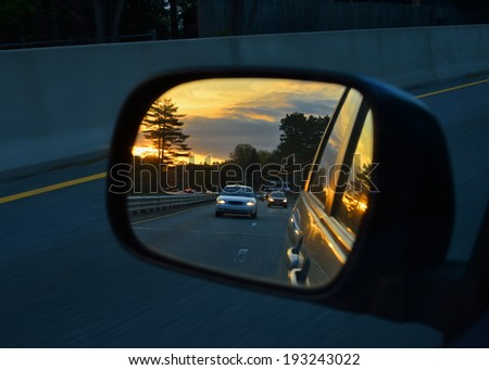 Highway traffic at dusk and sunset sky light reflected in rear view mirror - stock photo
