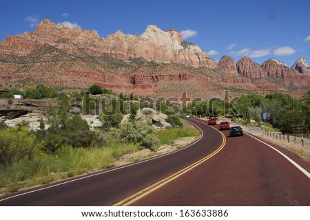Highway traffic driving beneath the mountains of Zion National Park, Utah