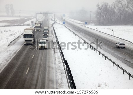 Highway traffic in heavy snowfall - stock photo