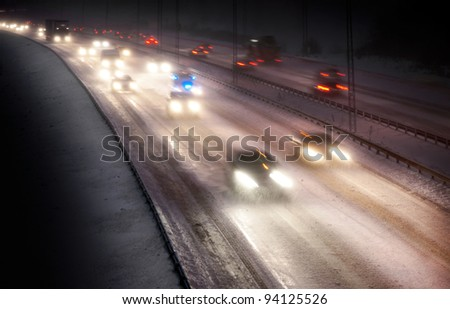 Highway traffic in snowstorm at night with blurred motion - stock photo