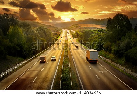 Highway traffic in sunset - stock photo