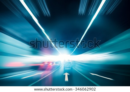 highway tunnel exit to light with speeding car motion blur - stock photo