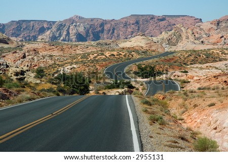 Highway Unfurls Like a Ribbon Across the Multi-Hued Desert Terrain