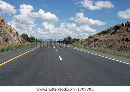 Highway with blue sky and vanishing point - stock photo