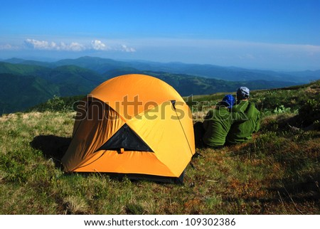 Hike in the Carpathian Mountains. The happy couple stopped to rest - stock photo