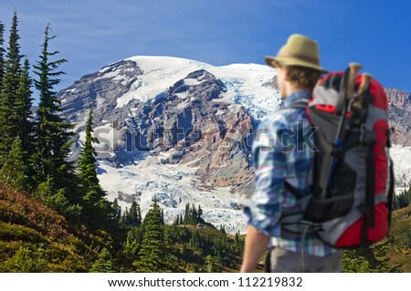 Hiker absorbing the magnificent view of Mount rainier. The hiker is out of focus, the view on the mountain is christal clear. - stock photo