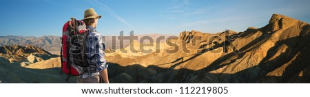 Hiker admiring the sunrise at Zabriskie point, Death valley, standing with his back to the camera, with a backpack and walking sticks on his back