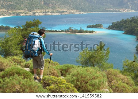 hiker against the blue-sky bay - stock photo
