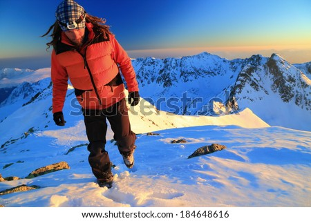 Hiker ascending snow covered mountain at sunset - stock photo