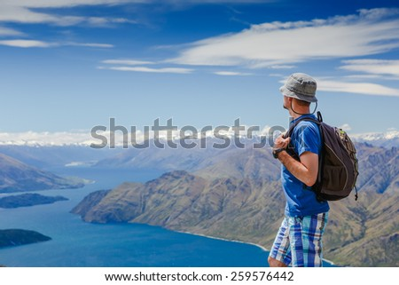 hiker at the top enjoy sunny day. New Zealand  - stock photo