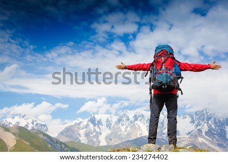 hiker at the top his hands raised enjoy sunny day  - stock photo