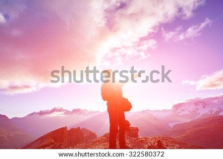 hiker at the top of a pass with backpack enjoy sunny day in Alps. Switzerland, Trek near Matterhorn mount. - stock photo
