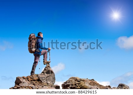 hiker at the top of a rock enjoy sunny day - stock photo
