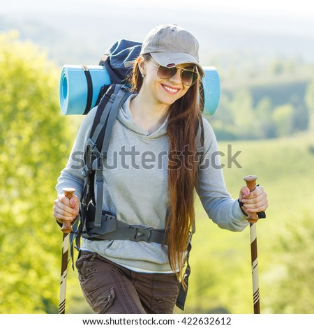 Hiker backpacker girl enjoying journey in countryside. Smiling girl in sunglasses walking with poles and backpack on hill - stock photo