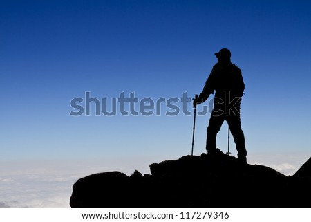 Hiker (backpacker) silhouette on top of a mountain with blue skyes. - stock photo