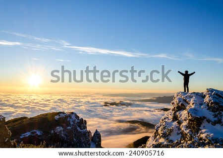 hiker celebrating success on top of a mountain in a majestic sunrise - stock photo