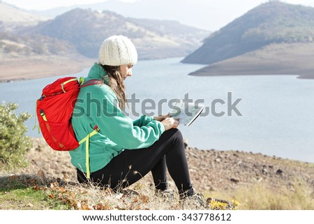 Hiker checking a route map - stock photo