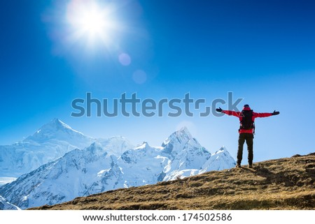 Hiker cheering elated and blissful with arms raised in the sky after hiking to mountain top summit above the mountains