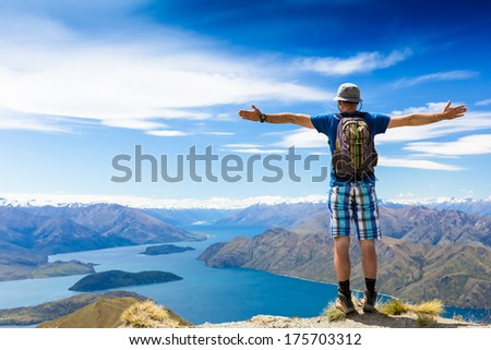 Hiker cheering elated and blissful with arms raised in the sky after hiking to mountain top summit above the clouds