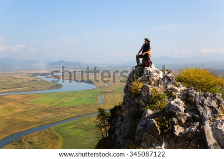 Hiker climbed a mountain and admire nature. Autumn morning.