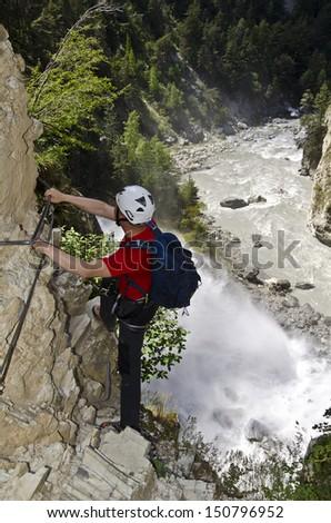 Hiker climbing a mountain near a waterfall - stock photo