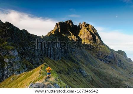 Hiker climbing on the ridge of Lofoten mountains, Norway - stock photo