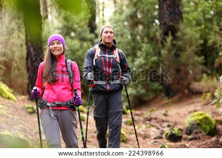 Hiker couple backpackers hiking in forest on path in mountains. - stock photo