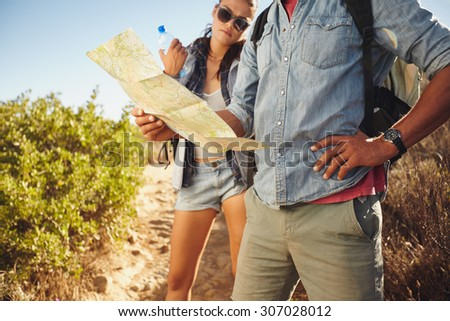 Hiker couple on country walk. Man with map and with woman standing my holding water bottle. Couple stopping to check their map while hiking in countryside.