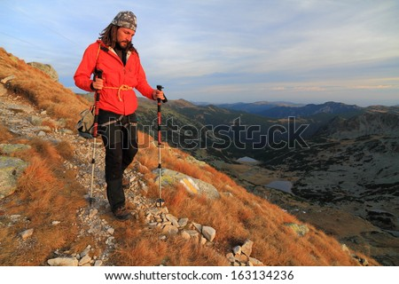 Hiker descending a mountain trail at sunset