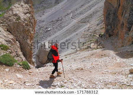 Hiker descending a rocky trail, Dolomite Alps, Italy